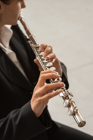 professional flute: Elegant woman playing a transverse flute, classical music professional