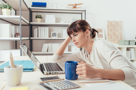 inefficient: Tired sleepy woman working at office desk and holding a cup of coffee, overwork and sleep deprivation concept