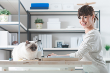 expressing positivity: Young woman at home, sitting at desk and working with a laptop, her cat is lying on the desktop, pets and lifestyle concept Stock Photo