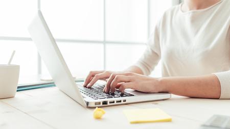 Vrouw zitten aan een bureau en werken op de computer handen close-up