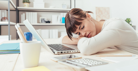 inefficient: Young tired woman at office desk sleeping with eyes closed, sleep deprivation and stressful life concept
