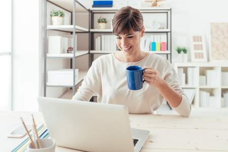 Young smiling woman at desk networking and connecting to internet using a laptop, she is having a coffee and holding a mug photo