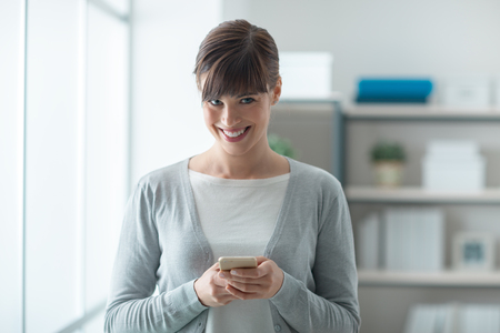 Smiling confident young woman texting with her mobile phone and looking at camera photo