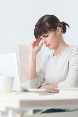 Sad tired woman having a bad headache, she is sitting at office desk and touching her temple photo