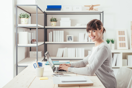Smiling confident businesswoman posing in her office, she is sitting at desk and typing with a laptop photo