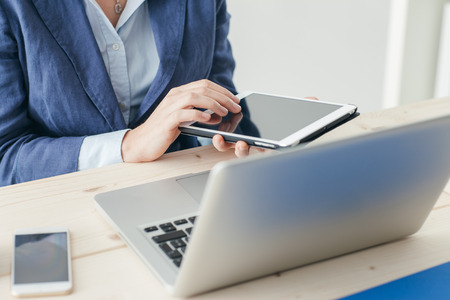 unrecognizable person: Businesswoman sitting at office desk, working with a laptop and using a touch screen tablet, hands close up, unrecognizable person