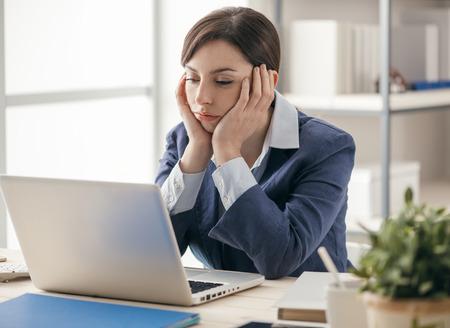 Empresaria aburrida deprimida que trabaja en el escritorio de oficina y establecimiento de una red con una computadora portátil, concepto de trabajo aburrido Foto de archivo