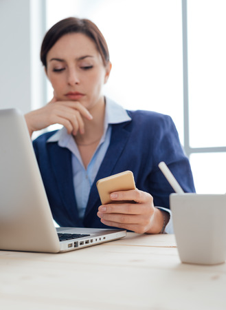 mobile sms: Pensive businesswoman working at office desk and reading sms on her mobile phone