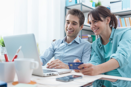 money online: Happy young couple at home surfing the web with a laptop and online shopping, she is holding a credit card, payments and transactions concept Stock Photo