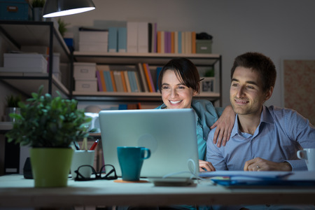 desktop computer: Happy smiling married couple at home using a laptop, connecting to internet and networking, communication and internet concept Stock Photo
