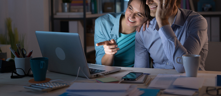 Young couple at home relaxing and watching a video on a laptop, she is pointing at the screen and smiling Stockfoto