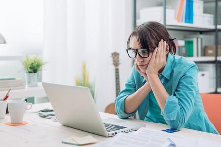 Mujer joven aburrido en la oficina de trabajo con un ordenador portátil y mirando a la pantalla del ordenador Foto de archivo