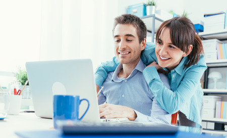 Young happy couple at home using a laptop and surfing the web, they are enjoying and social networking, technology and togetherness concept