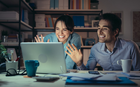 Young couple at home using a laptop, they are video calling their friends and greeting them, communication and friendship concept