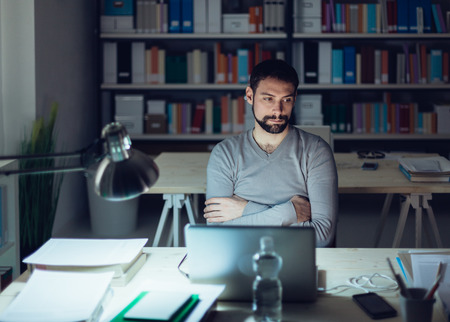 working overtime: Pensive young man sitting at office desk and working overtime late at night, he is thinking with arms crossed Stock Photo