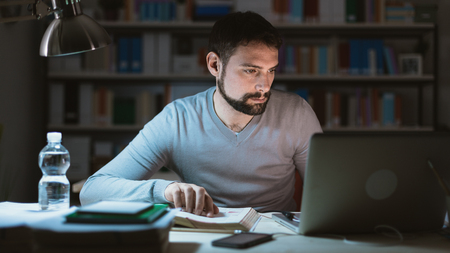 man studying: Young man sitting at desk, using a laptop, working late at night, he is studying a book and using a laptop Stock Photo