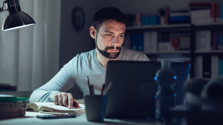 Young man sitting at desk, using a laptop, working late at night, he is studying a book and using a laptop Stockfoto