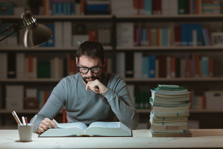 Zelfverzekerd volwassen student in de bibliotheek 's avonds laat, zit hij op het bureau en het lezen van een boek met de hand op de kin, leren en onderwijs concept