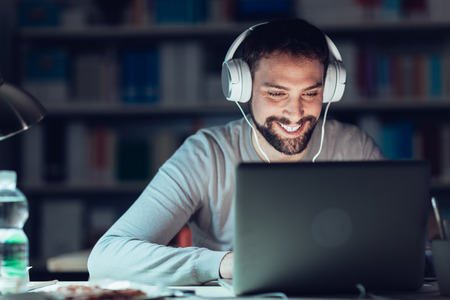 Young smiling man networking and connecting to internet using a laptop late at night, he is sitting at desk and wearing headphones Stockfoto