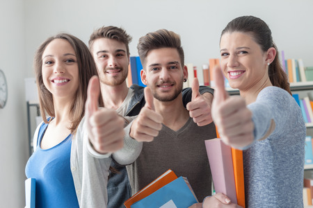 young group: Cheerful group of students smiling at camera with thumbs up, success and learning concept