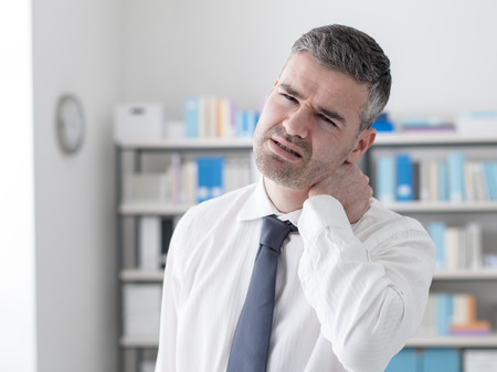 working stiff: Sad businessman having neck pain symptoms, he is touching his neck, health care and illness concept Stock Photo