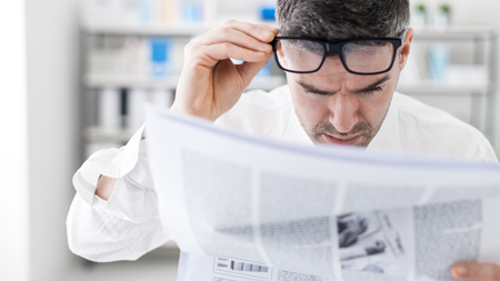 editor: Businessman in the office, reading bad breaking news on a financial newspaper, he is shocked and adjusting his glasses
