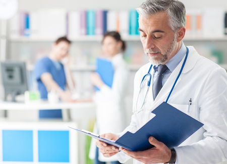 Confident professional doctor in the office checking patient's medical records on a clipboard, medical staff working on the background