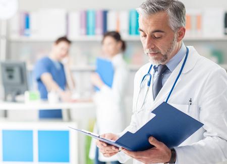 Zekere professionele dokter in het kantoor controleren de medische dossiers van de patiënt op een klembord, medisch personeel dat op de achtergrond werkt Stockfoto