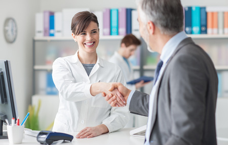 Patient shaking hands with a female doctor at the clinic reception, healthcare and customer satisfaction concept