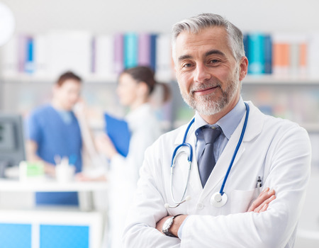 Confident smiling doctor posing and looking at camera with arms crossed, medical staff working on the background