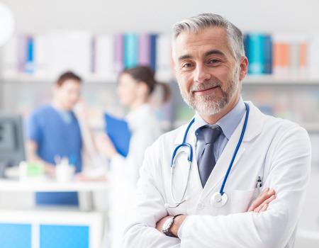 Zekere glimlachende dokter poseren en kijken naar de camera met de armen gekruist, medisch personeel dat werkzaam is op de achtergrond Stockfoto