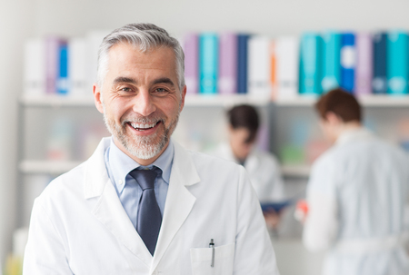 physician: Smiling confident doctor looking at camera and posing in the office, medical staff working on the background Stock Photo