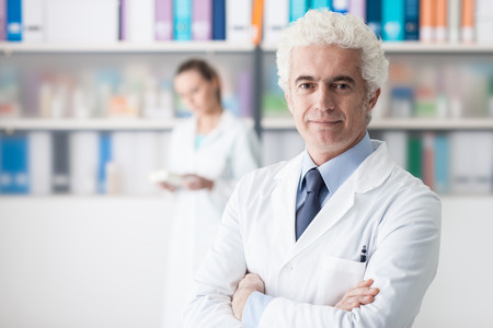 Confident doctor posing in his office and smiling at camera, his assistant is working on the background