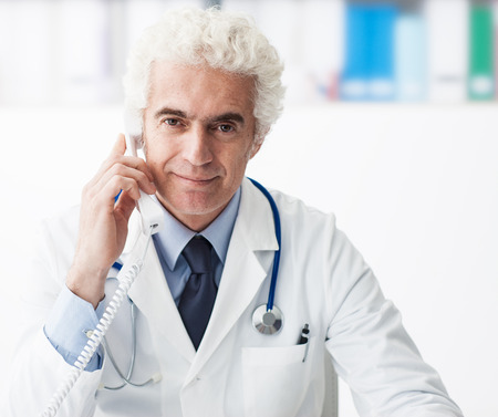 phone calls: Confident doctor sitting at office desk and answering phone calls, consulting and healthcare concept