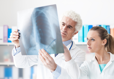 radiologist: Radiologist checking an x-ray with his assistant in his office, healthcare and prevention concept