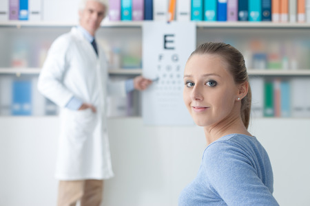 testing vision: Young woman in the optometrist office examining her eyesight, he is pointing at the chart, eye care concept Stock Photo