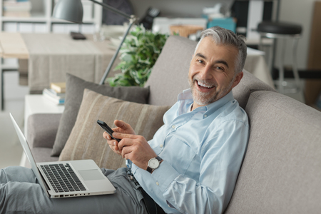 laptop home: Confident businessman working at home, he is sitting on the sofa with a laptop on his lap and using a smartphone