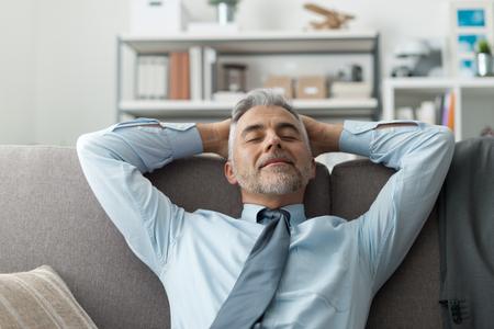 El hombre de negocios en su casa de descanso y relajación en el sofá con las manos detrás de la cabeza Foto de archivo - 63504541