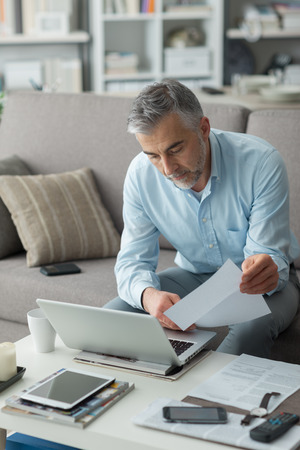 executive apartment: Businessman at home, he is working with a laptop, checking paperwork and bills