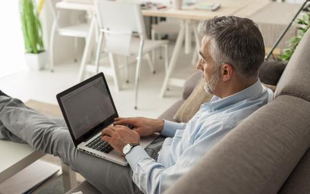 usando computadora: El hombre de negocios en su casa sentado en el sofá con los pies y trabajan con su computadora portátil