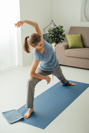 side angle pose: Yoga workout at home in the living room, a woman is exercising on the mat, healthy lifestyle concept