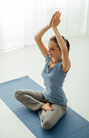 hands clasped: Woman practicing yoga and meditation at home on the floor, she is sitting with hands clasped