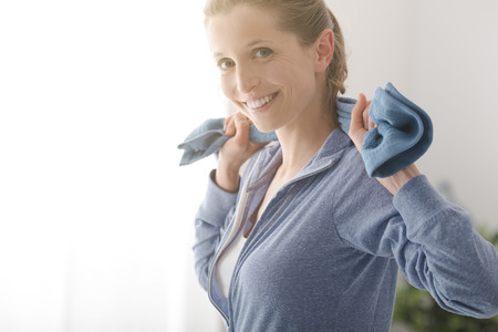 sport fitness: Confident sportswoman posing with a towel and smiling at camera, healthy lifestyle and fitness concept