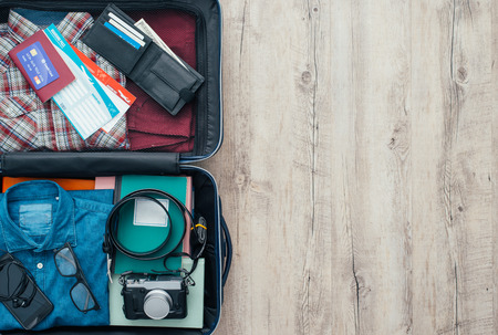 Open traveler's bag with clothing, accessories, credit card, tickets and passport, travel and vacations concept, flat lay Foto de archivo