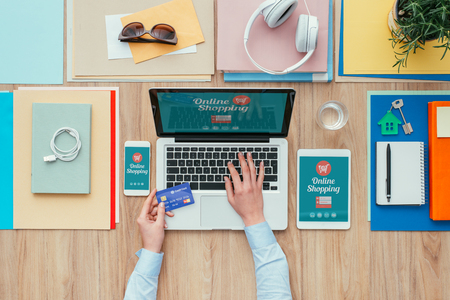 Woman working at office desk with a laptop and shopping online, she is using a credit card, e-commerce and electronic payments concept