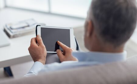 tapping: Man sitting on the couch and using a digital touch screen tablet, he is tapping with his finger Stock Photo