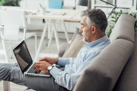 executive apartment: Businessman at home sitting on the couch with feet up and working with his laptop