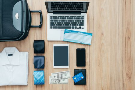 formal clothing: Businessman getting ready to leave for a business trip and packing a bag with formal clothing, accessories, laptop and plane tickets, traveling and business concept, flat lay Stock Photo