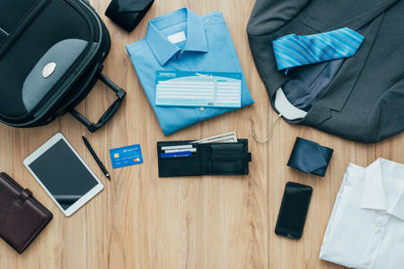 How to pack for a business trip: all items that needs to be packed and a bag on a desktop, travel concept