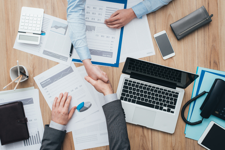 Zakenmensen werken op kantoor en geven een handdruk, samenwerkings- en akkoordconcept